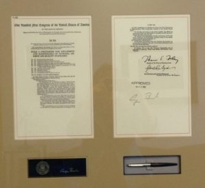 Ceremonial pen and papers in a frame.